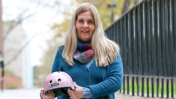 Professor Lori Buchanan holds a bicycle helmet, painted as part of the Brain Bucket research project of recent Master's graduate Daniella Mlinarevic.