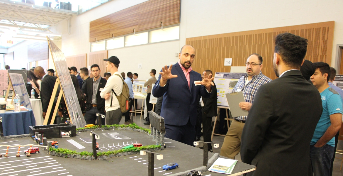 Habib Haider explains his group project, a system designed to reduce the impact of long lines waiting to access the Gordie Howe International Bridge, to professor Hanna Maoh of the Cross-Border Institute.