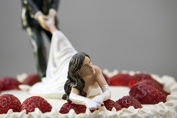 wedding cake topper depicting groom dragging reluctant bride