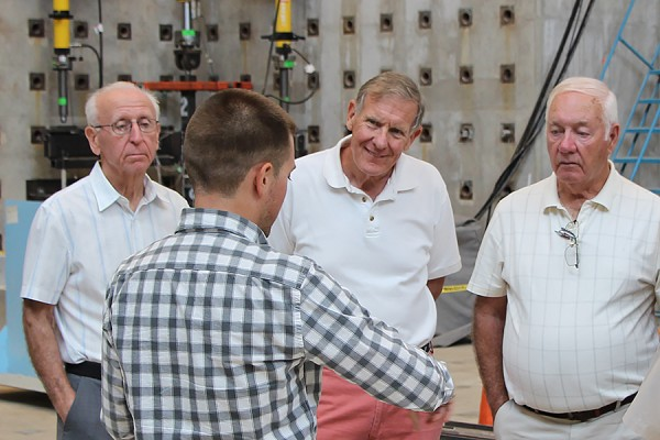 Second-year civil engineering student Jason Duic speaks with alumni David Strelchuk, Philip Waier, and Henry Regts.