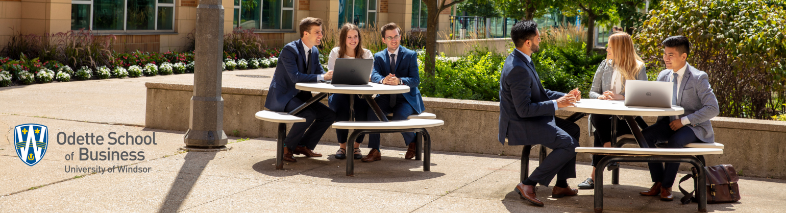 Business students sitting at picnic tables outside of the Odette School of Business building.
