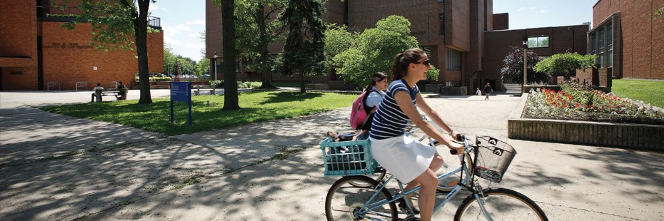 Two students riding bicycles on campus