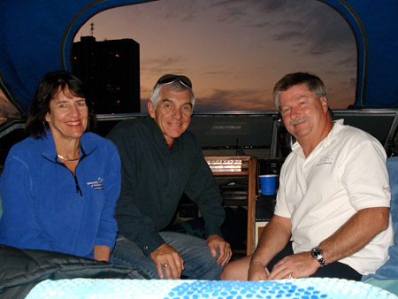 Dorothy Spiller, Alan Wright and Rick Kiza sit in a boat.  Sun setting in background.