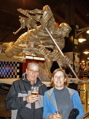Gordon and Julie Joughin stand in front of a statue of the legendary Gordie Howe.