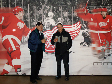 Alan and Gordon pose in front of a giant poster featuring players from of the famous Red Wings hockey club.
