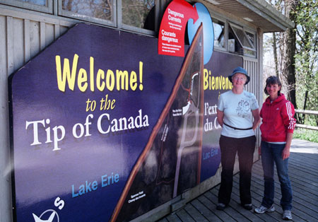 Alison Holmes and Marie-Jeanne Monette by large sign that reads: Welcome to the Tip of Canada.