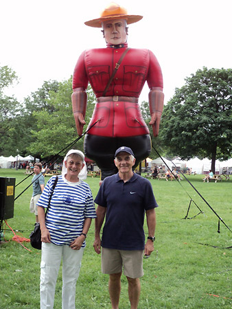 Patsy Paxton and Alan Wright stand in front of a 15 foot high inflatable RCMP officer at Willistead Manor.