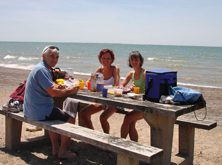 Alan Wright, Marianne Poumay and Marie-Jeanne Monette sitting at picnic table.