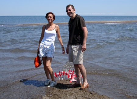 Marianne Poumay and François Georges posing at the southernmost tip of Canada. On the ground beneath them are numerous small Canadian flags planted into the sand.