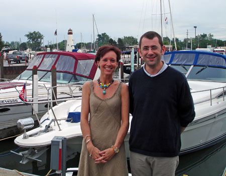 Marianne Poumay and François Georges stand on a dock with boats in the background.