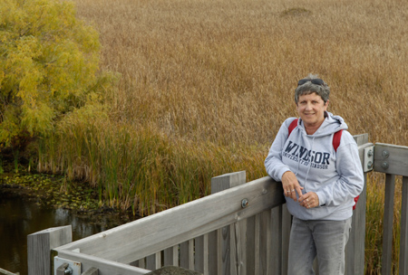 Sue Purnell stands on beach at Point Pelee National Park with the point in the background.