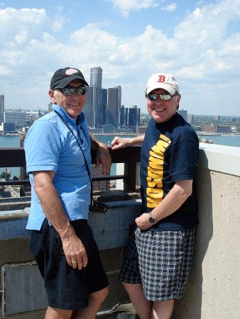 Alan Wright and Mark Schofield pose on the rooftop of a building with the Detroit skyline in the background.