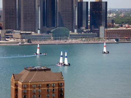 A plane is about to fly through two inflated pylons on the Detroit River. The Renaissance Center is in the background.