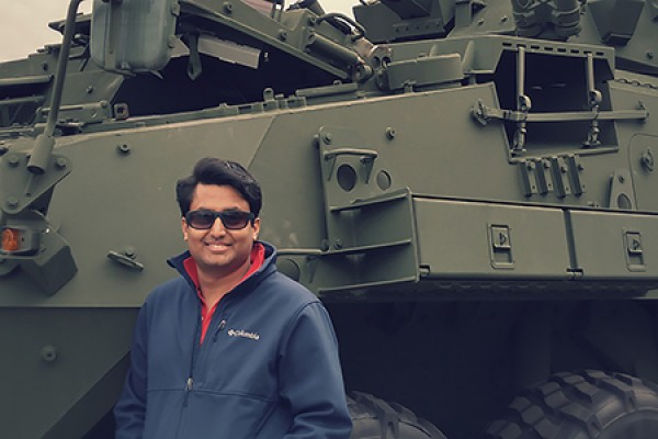 young man posed in front of tank