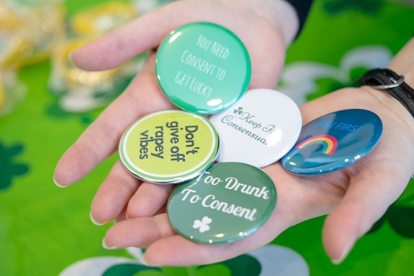 handfuls of buttons bearing messages about sexual consent