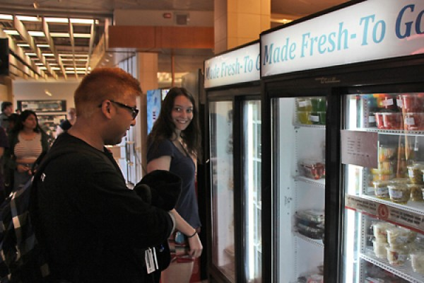 Students Shane Gonsalves and Rachel Pieniazek look into coolers.