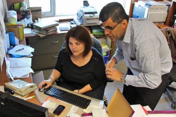 Susan Rotondi and Maher El-Masri shuffle papers at desk