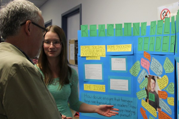Education student Sarah McGuire explains her project during Friday's poster exhibit.