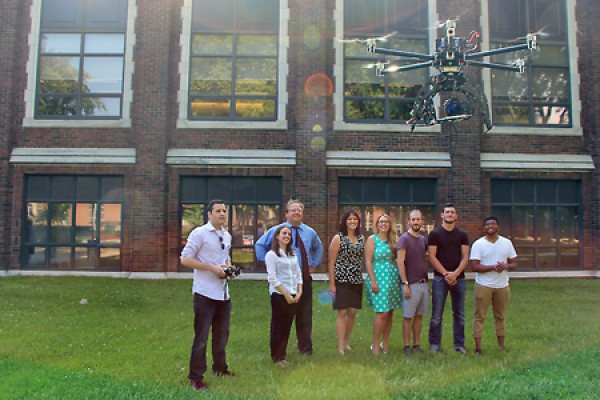 Students and staff watch drone hover outside Dillon Hall.