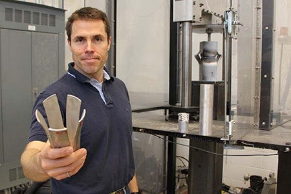 Engineering professor Bill Altenhof holds a metal tube.