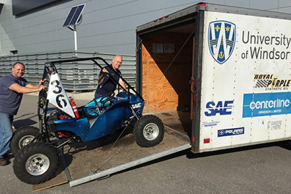 Dean Poublon and Bruce Durfy load the student-designed and -built Baja vehicle into a truck.