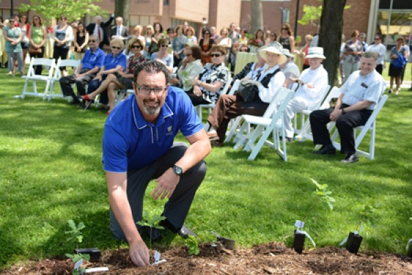 Alumni association president Mike Bates plants a tree seedling