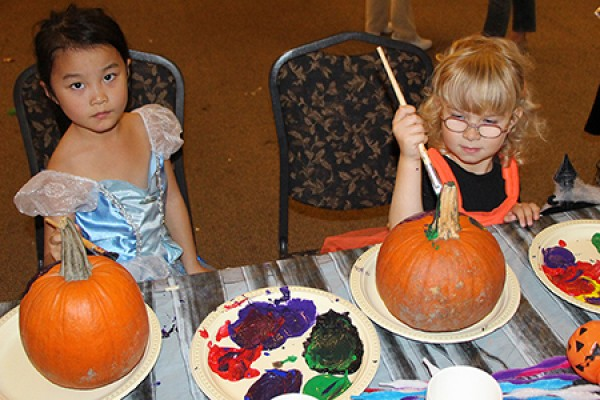 Kids in costume painting pumpkins