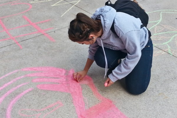 engineering student Julia Costa chalks a message