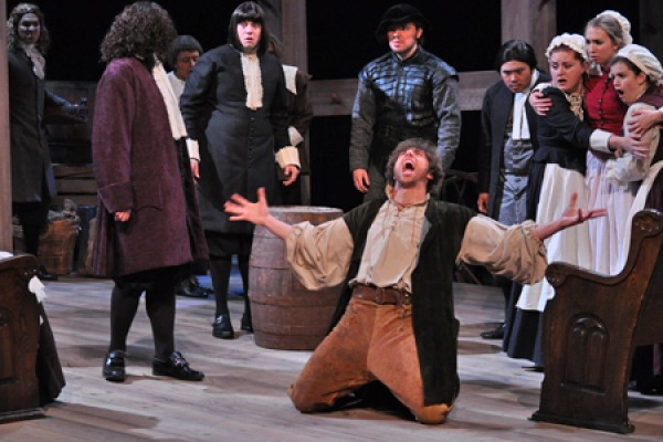John Proctor (Mauro Meo) takes to his knees
