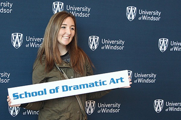 "Megan Lovell holding sign ""Dramatic Art"""