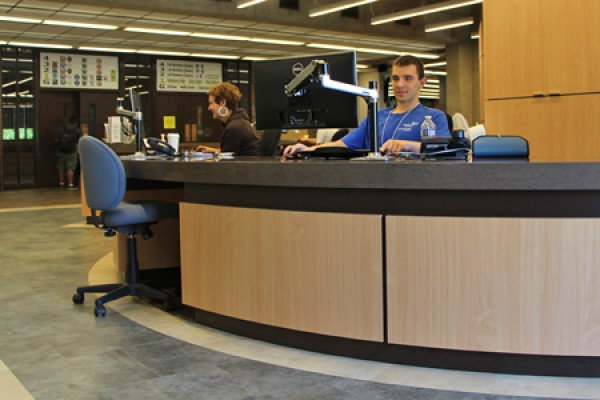 Librarian Selinda Berg and student IT consultant Tomas Dobos staff the Leddy Library service desk.