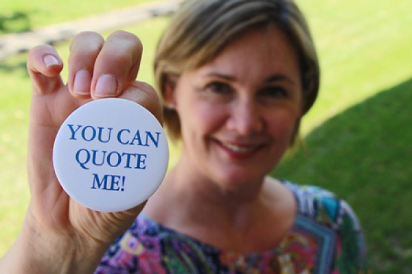 "Lori Lewis holding up button that reads ""You can quote me!"""