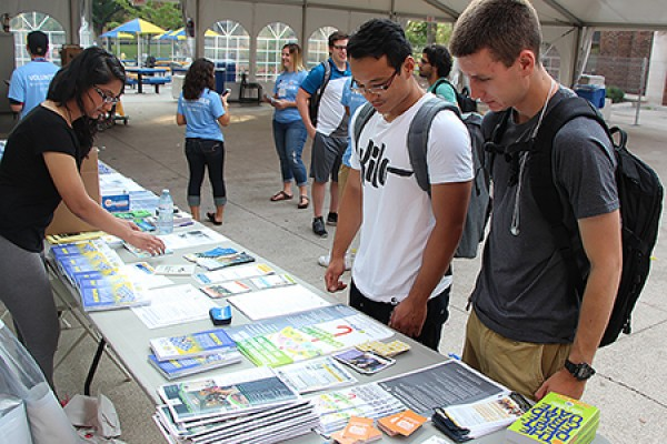 Event coordinator Amber Shaheen gathers some UWindsor Welcome Week material for Luc Nguyen and Derek McCaffrey at the info station, set up in the tent between Memorial and Dillon halls.