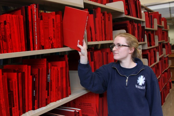 student Melanie Grondin pulls a book from a shelf