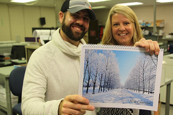 Scott Thorpe and Jen Almeida of the University Print Shop brandish a custom calendar of the sort they can design for holiday gift-givers.