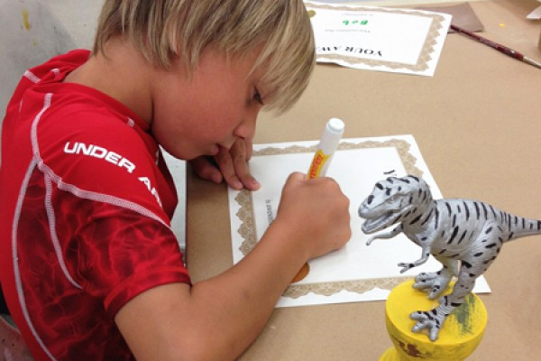 student working on dinosaur trophy