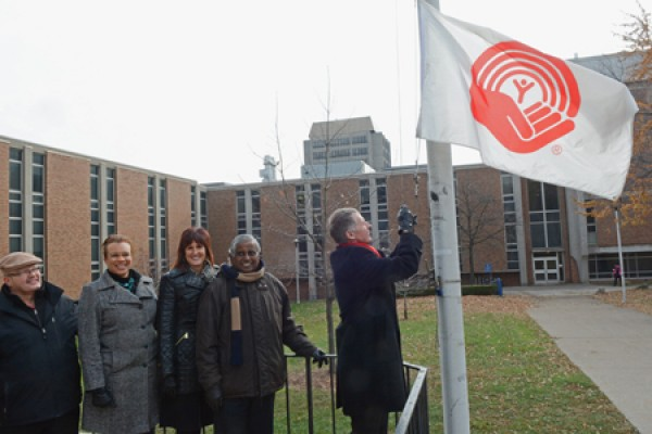 UWindsor president Alan Wildeman raises the United Way flag.