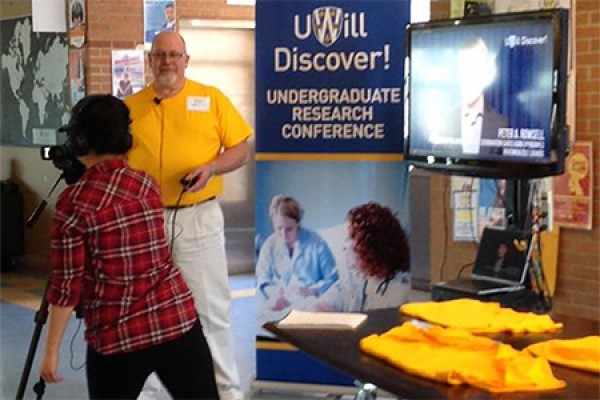 Chair Simon du Toit poses at the entrance to last year's UWill Discover undergraduate research conference.
