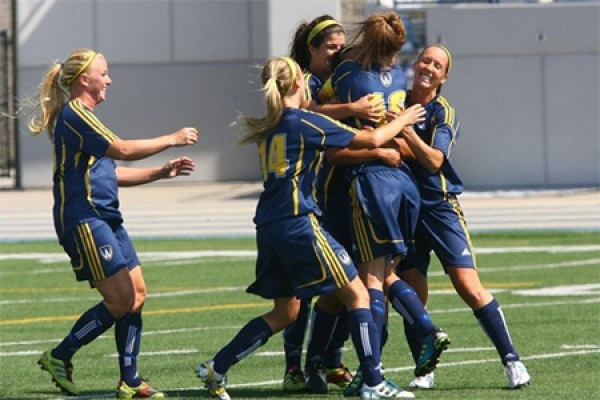 Lancer women's soccer players hug and jump.