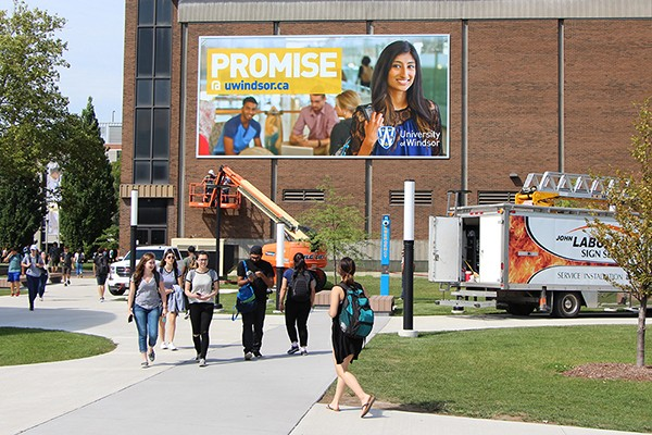 giant banner bearing image of student and words Promise@UWindsor