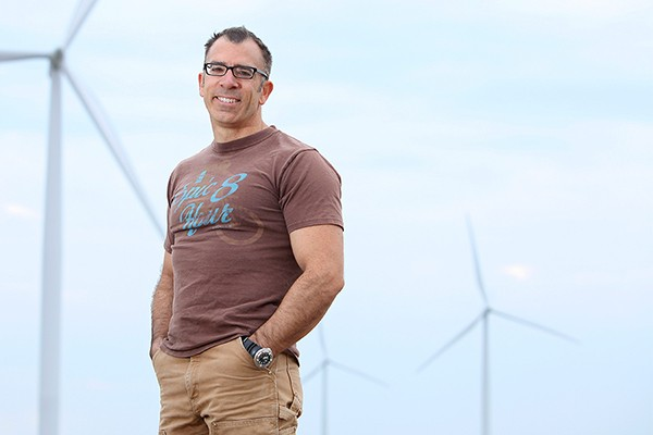 Engineering professor Rupp Carriveau stands before a Kruger Energy wind farm in Chatham-Kent.