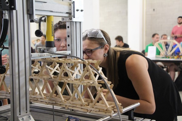 During the fourth annual popsicle stick bridge building contest, third year Civil engineering student Laura Daniel made sure her team's structure is placed correctly in a specially-built machine that measures the force applied as the structures are crushe