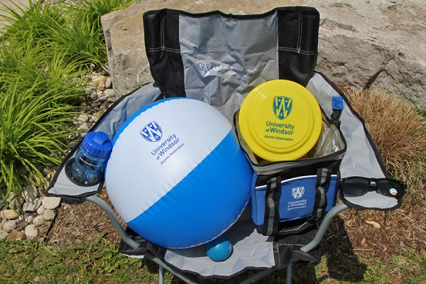 folding lawn chair, insulated cooler bag, polarized sunglasses, water bottle, inflatable beach ball, flying disk, and rubber stress ball: all bearing the alumni association logo