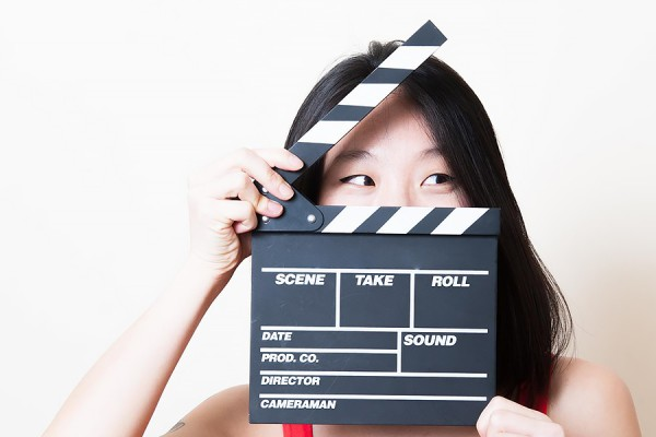 woman holding clapboard before her face