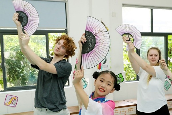 Education students George Paterson and Caroline Voyer follow a youthful instructor through a traditional dance during their visit to Changlang Primary School in Suzhou, China.