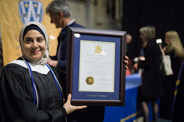 woman in grad robes holding framed diploma