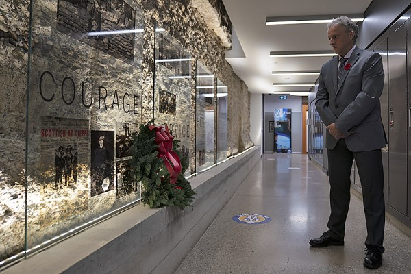 UWindsor president Robert Gordon lays a wreath under a tribute to the courage and sacrifice of those who served.