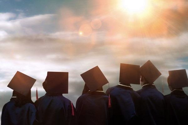 Graduates in mortarboards silhouetted against sunny sky