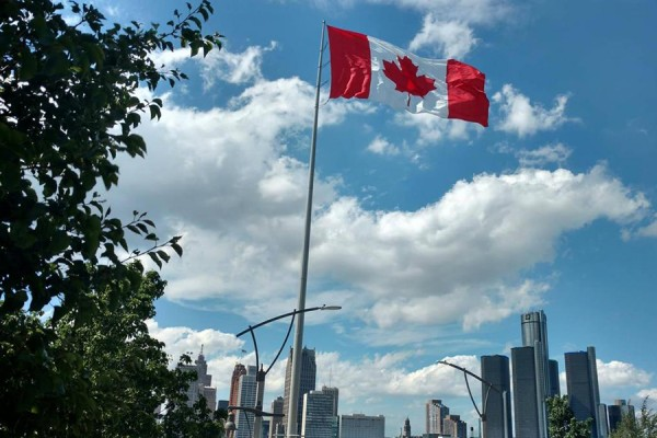 Canadian flag flying against Detroit skyline