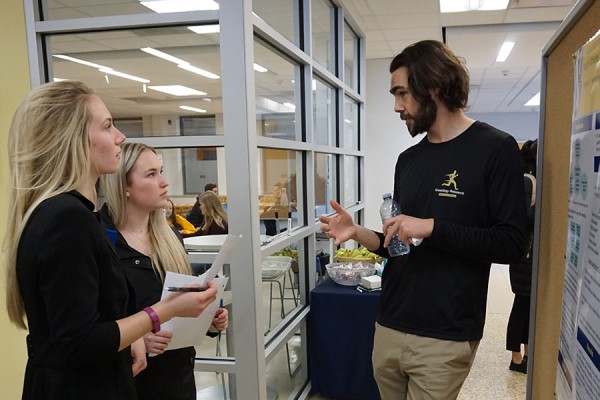 Grad student Kieran Hawksley describes his research project to two students.